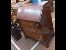 A walnut bureau with drawers below