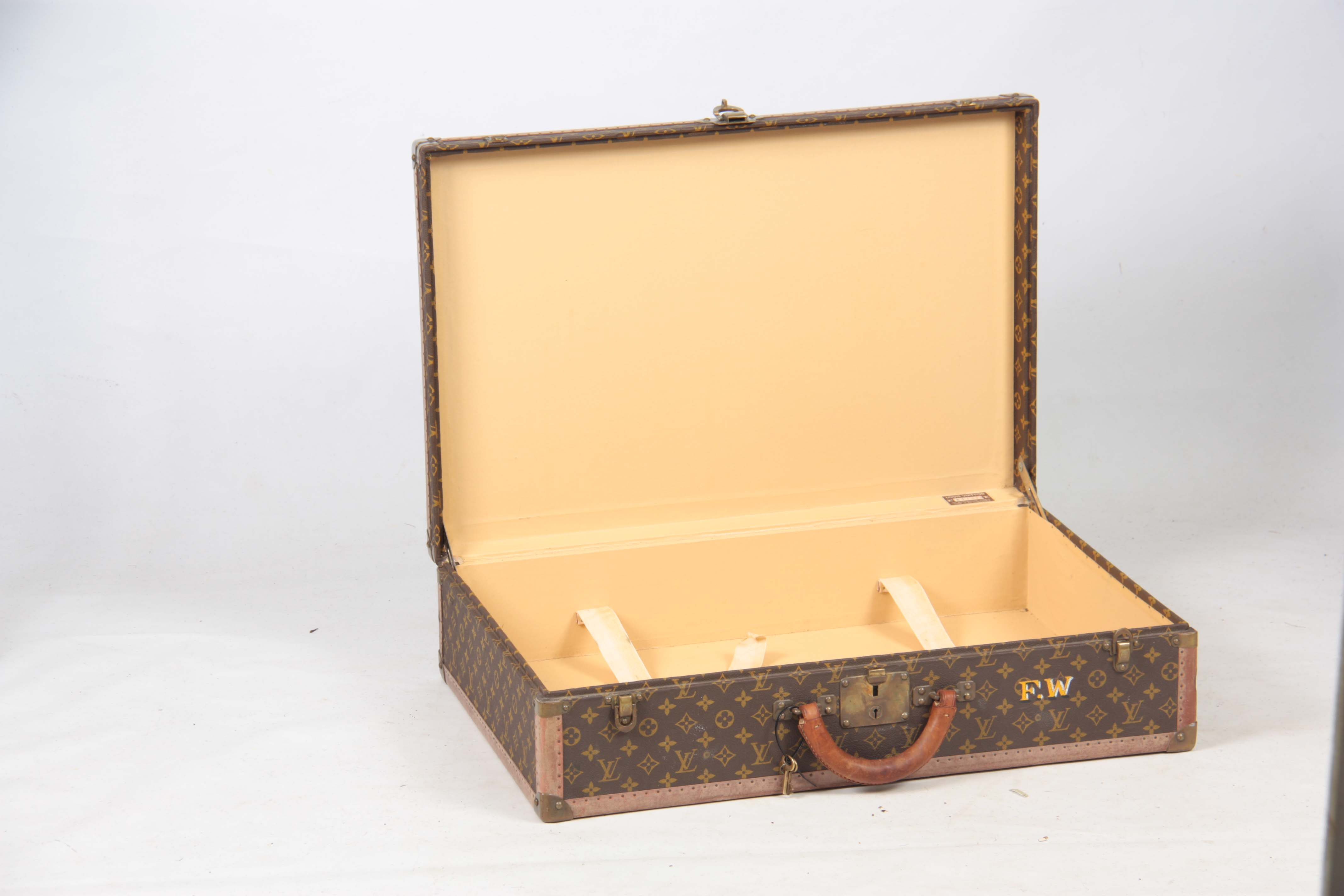 Lot 520 - A VINTAGE LOUIS VUITTON BROWN LEATHER SUITCASE with studded brass corner mounts, fasteners and