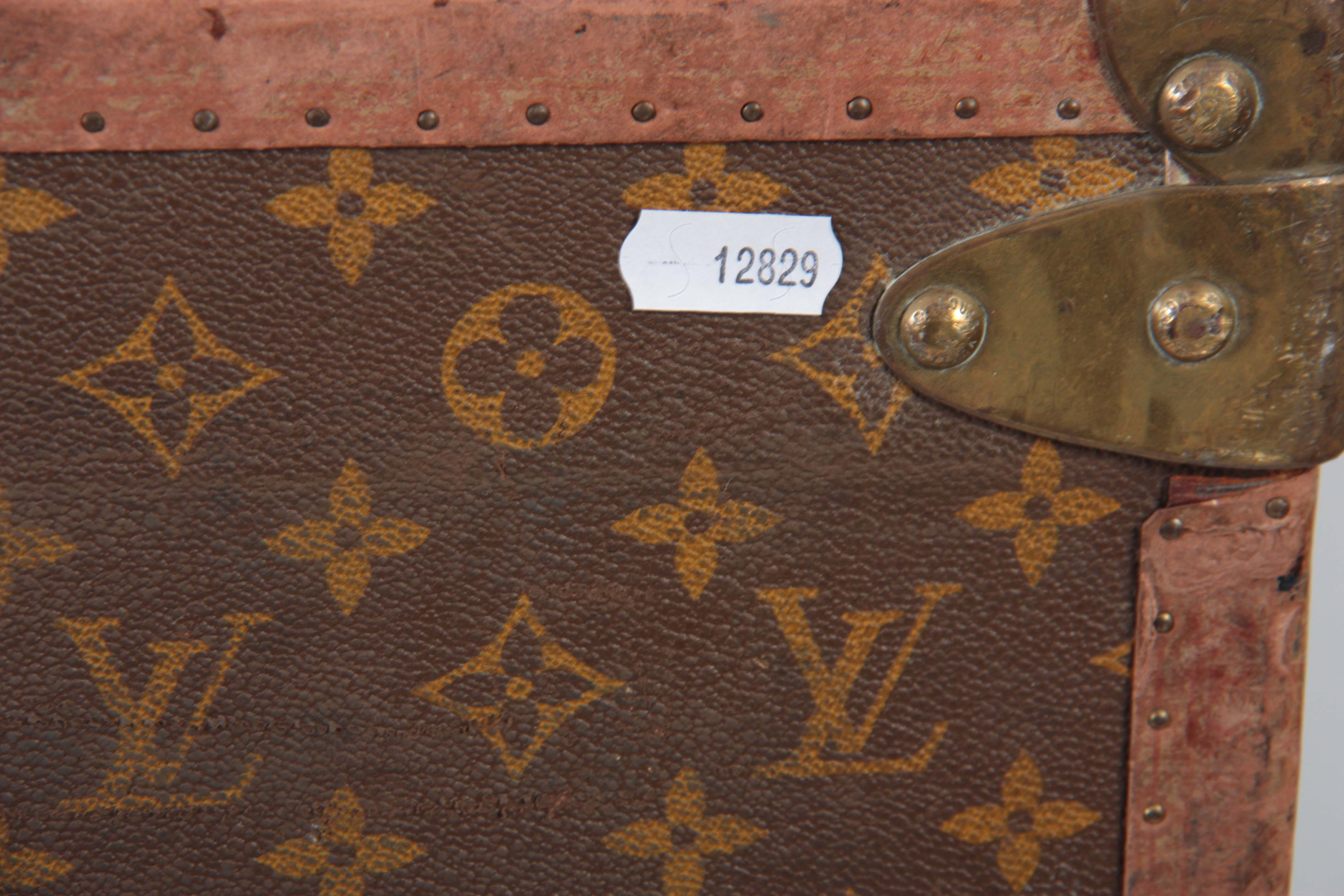 Lot 519 - A VINTAGE LOUIS VUITTON BROWN LEATHER SUITCASE with studded brass corner mounts and angle straps