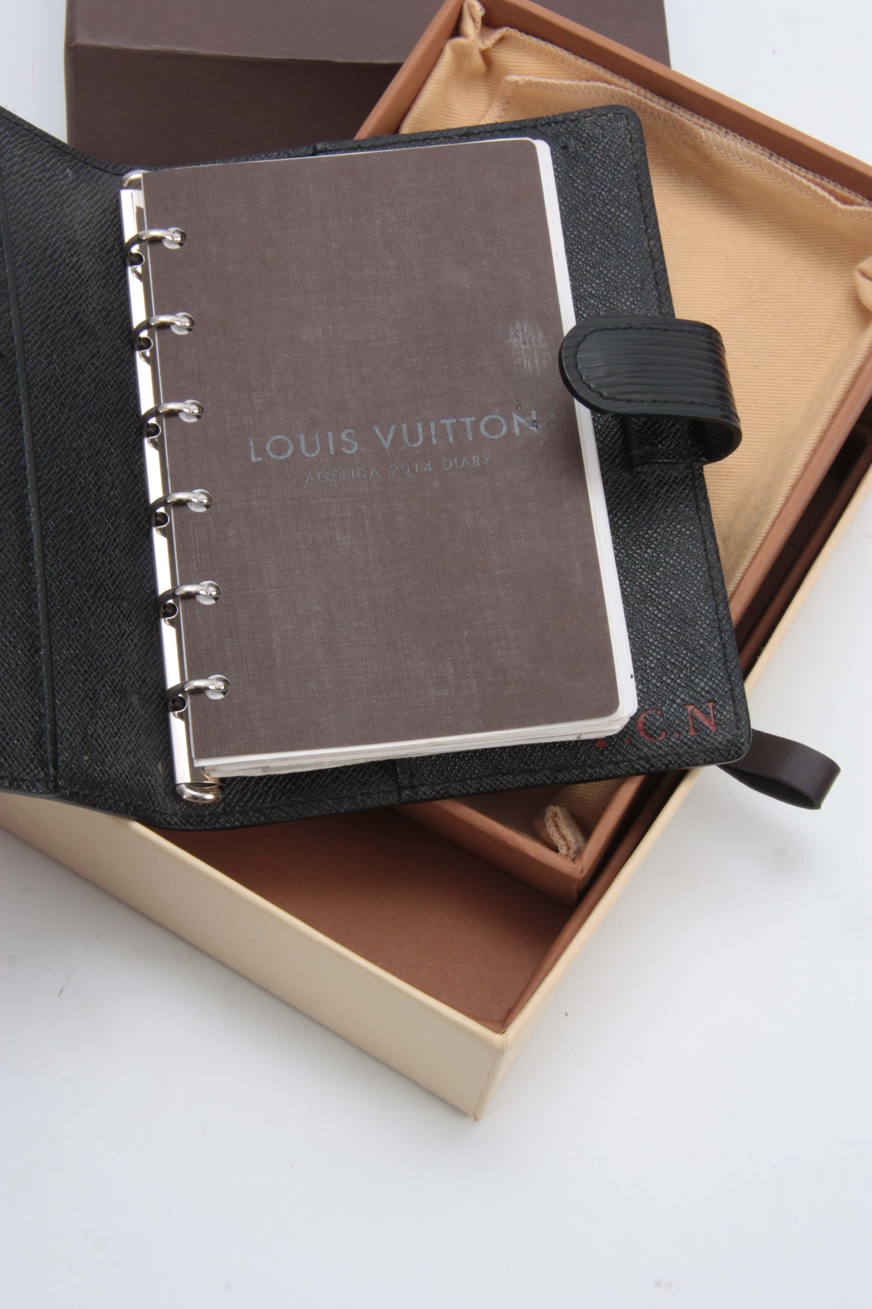 Lot 518 - A LOUIS VUITTON GRAINED BLACK LEATHER FOLDING DIARY for 2014 with sprung ring holders 14.5by18cm -