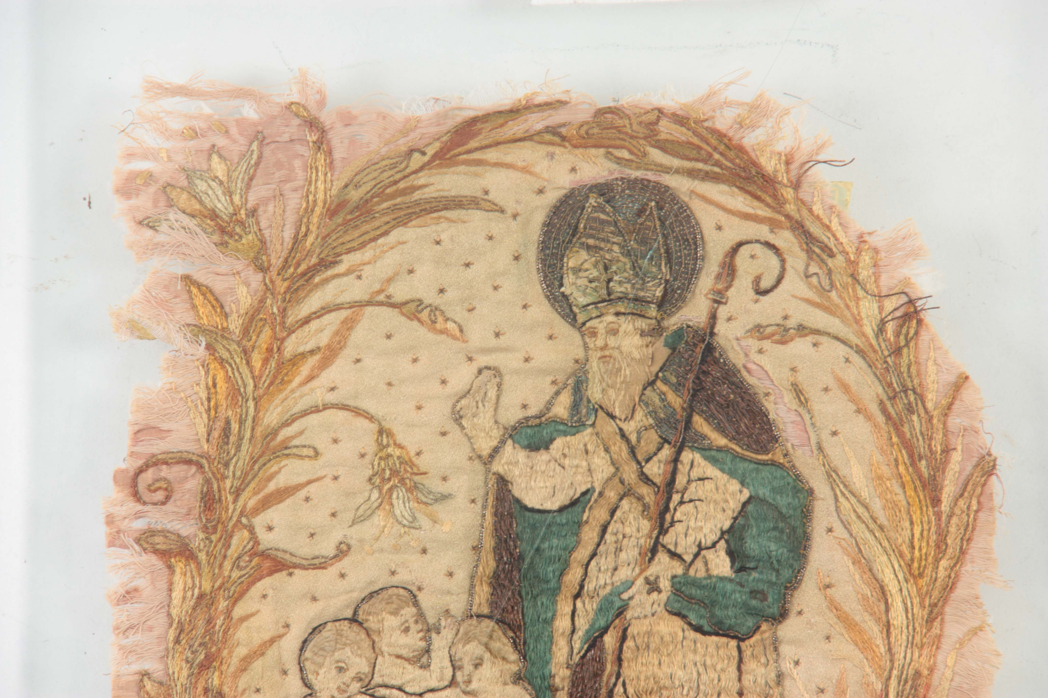 Lot 652 - A 17TH CENTURY SILK EMBROIDERED STUMPWORK PANEL depicting a standing Saint with three infants in a