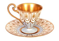 A ROYAL WORCESTER CABINET CUP AND SAUCER with pale blue and gilt jewel Adam style panelled