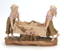 A LATE 19TH CENTURY ROYAL DUX BOHEMIAN FIGURAL TABLE CENTREPIECE modelled as a girl and boy