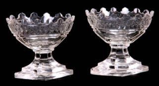 A PAIR OF GEORGIAN CUT GLASS TABLE SALTS the diamond-shaped stepped pedestal bases supporting oval