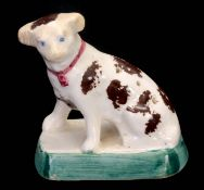 A 19TH CENTURY STAFFORDSHIRE POTTERY HATPIN HOLDER FORMED AS A DOG decorated with brown spots,