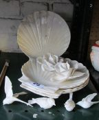 Four Belleek shell plates (a/f) and two white porcelain flower heads and birds