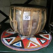 An African drum and a beaded circular hanging