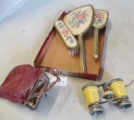A pair of pseudo ivory clad opera glasses and an embroidered dressing table set