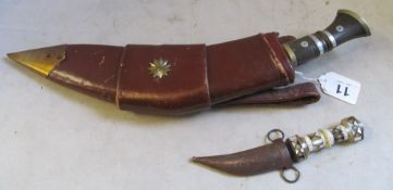 A dagger in a leather holster signed military with two small daggers and a small mother of pearl