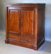A 20th Century Hardwood Side Cabinet with two panel doors above two drawers raised upon a plinth