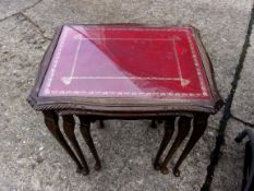 A nest of three side tables, red and gold leather inlaid with glass tops. An attractive set.