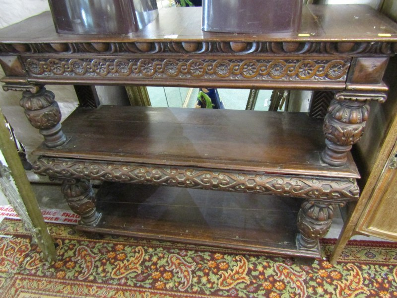 Lot 685 - ANTIQUE OAK BUFFET, carved oak triple shelved buffet with cup and cover design and 2 frieze drawers,