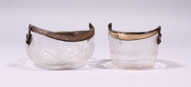 TWO CONTINENTAL CUT GLASS CIRCULAR BASKETS, with silver swing handles.