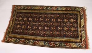 A PERSIAN CAUCASIAN RUG, EARLY 20TH CENTURY, black ground with five rows of gulls, within a beige