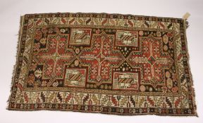 A PERSIAN CAUCASIAN RUG, EARLY 20TH CENTURY, with three large cross shaped medallions, within a