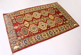 A MODERN PERSIAN RUG, rust ground with two rows of five large medallions. 6ft 3ins x 3ft 11ins.