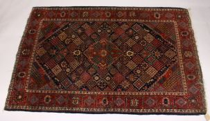 A KASHAN RUG, 20th Century dark blue ground with allover stylized emblems. 6ft 8ins x 4ft 3ins.