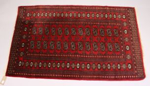 A MODERN BOKHARA STYLE RUG, red ground with two rows of thirteen gulls. 5ft 1ins x 3ft 2ins.