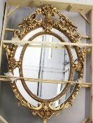 A LARGE AND IMPRESSIVE FRENCH STYLE GILT FRAMED OVAL WALL MIRROR, with highly ornate frame. 7ft 4ins