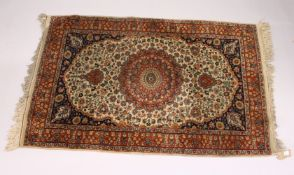 A SMALL KASHAN RUG, 20th Century beige ground with floral decoration, with a similar rust ground