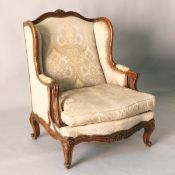 A LATE 19TH CENTURY FRENCH CARVED BEECH FRAMED WING BACK ARMCHAIR, upholstered with a classical