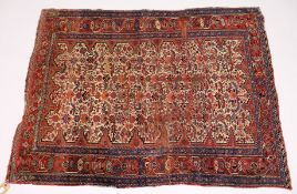 A PERSIAN RUG, early 20th Century, beige ground woven with stylized animals and birds, within a rust