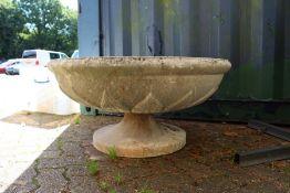 A large circular pedestal reconstituted stone garden urn.