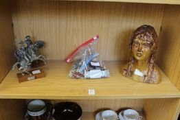 Two cast metal figures, toy cars and a pottery bust of a young girl.