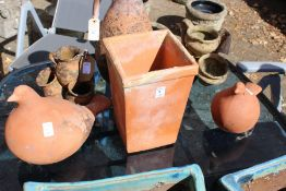 A pair of terracotta bird shaped garden ornaments and a square shaped pot.