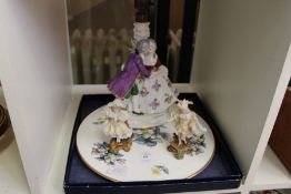 A porcelain figural lamp, a pair of figures and a boxed porcelain stand.
