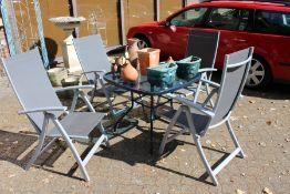 A garden table and four folding chairs.