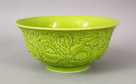 A CHINESE GREEN GLAZED PORCELAIN DRAGON BOWL, with moulded decoration of dragons amongst stylized