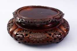 A GOOD 19TH CENTURY CHINESE CARVED HARDWOOD STAND, carved with sceens of flora, 32cm diameter ,