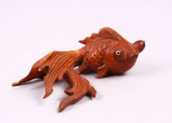 A CHINESE CARVED BOXWOOD/ WOODEN FIGURE OF A GOLDFISH, with glass inset eyes, 3cm x 8cm.