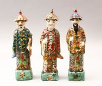 THREE 19TH / 20TH CENTURY CHINESE FAMILLE VERTE PORCELAIN FIGURES, each wearing hats with bead