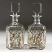 A GOOD PAIR OF BACARAT GILDED DECANTERS AND STOPPERS.