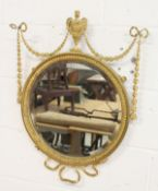 A REGENCY DESIGN GILT FRAMED CIRCULAR MIRROR, 19TH CENTURY, with urn finial, ribbon and harebell