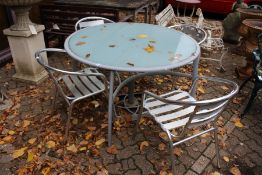 A modern circular patio table and four chairs.