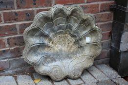 A shell shaped birdbath top.