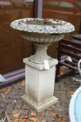 A good large reconstituted stone urn on a pedestal base.