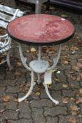 A small cast iron garden table with circular top.