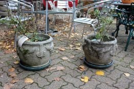 A pair of reconstituted stone garden pots.