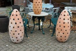 A large pair of terracotta garden floor standing lanterns with pierced star shaped decoration.