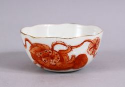 A 19TH / 20TH CENTURY CHINESE IRON RED PORCELAIN WINE CUP, decorated with lion dogs playing, the