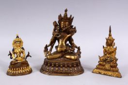 THREE TIBETAN GILT BRONZE FIGURES, each with varying pose, the smallest with poly chrome decoration,
