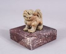 A CHINESE 19TH / 20TH CENTURY CARVED SOAPSTONE LION DOG SEAL, the dog upon plinth, the base cared