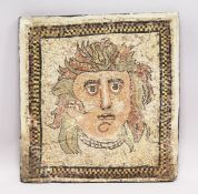 A SMALL RUSSIAN MOSAIC STONEWARE PANEL depicting a head. 1ft 9in x 1ft 8ins.