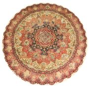 A GOOD PERSIAN CIRCULAR CARPET, with a large floral central motif, surrounded by small vignettes