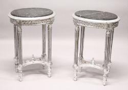 A PAIR OF FRENCH STYLE CARVED AND SILVERED WOOD LAMP TABLES, with oval marble tops. 2ft 4ins high