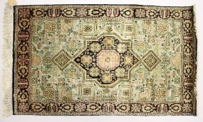 A SMALL PERSIAN SILK RUG, 20TH CENTURY, with a central star shape motif and decorated with